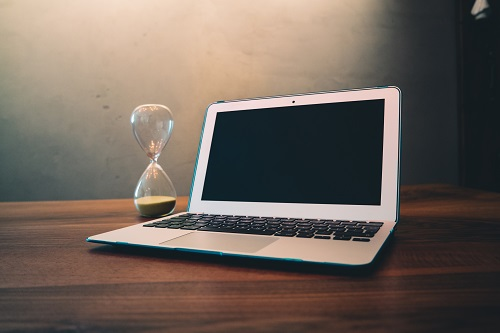 hourglass and laptop