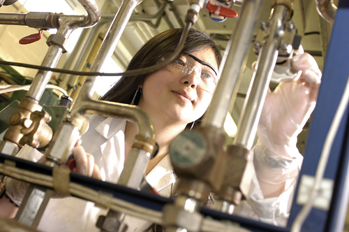 student in lab with distillation equipment